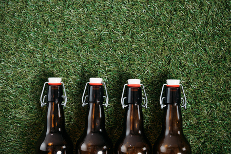 Above view of cold beer bottles lying on grass