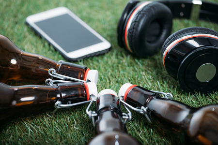 Closeup view of beer bottles with smartphone and headphones lying on grass