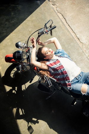beautiful sensual young woman in denim vest lying on motorbike Stock Photo - 83106366