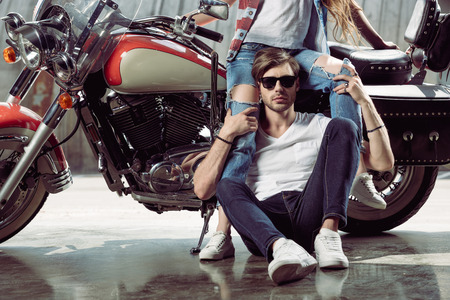 young woman sitting on motorcycle and stylish man in sunglasses looking at camera