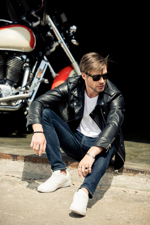 stylish young man in leather jacket and sunglasses sitting on concrete curb near motorbike Stock fotó - 83189168
