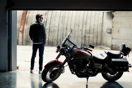 오토바이 근처에 서서 멀리보고 가죽 자켓에 세련된 젊은이