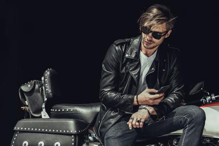 오토바이에 앉아서 스마트 폰을 사용하는 선글라스와 가죽 자켓에 젊은이