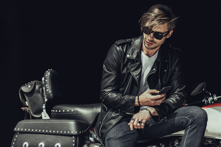 young man in sunglasses and leather jacket sitting on motorbike and using smartphone Reklamní fotografie