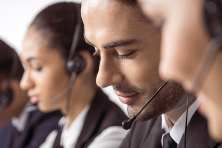 call center operators in headsets working together