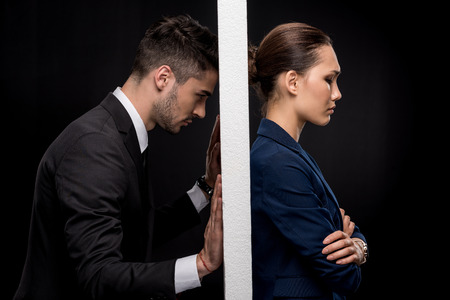 Side view of sad couple in formal wear separated by wall