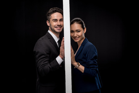 Side view of young smiling couple separated by wall and looking at camera