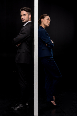 Side view of confident couple standing back to back near of separated wall