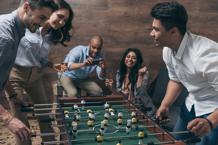 young friends playing table football together indoors