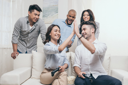 multiethnic friends playing video games and giving high five at home Stock Photo