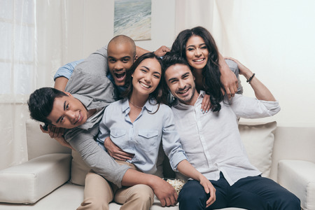 cheerful multiethnic friends embracing while sitting on sofa at home Stok Fotoğraf