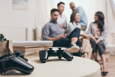 casual multiethnic friends sitting on sofa with joysticks on foreground