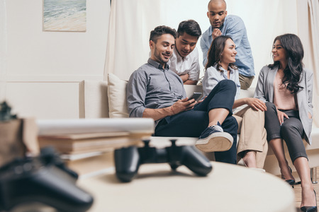 casual multiethnic friends spending time together while sitting on sofa at home Stock Photo