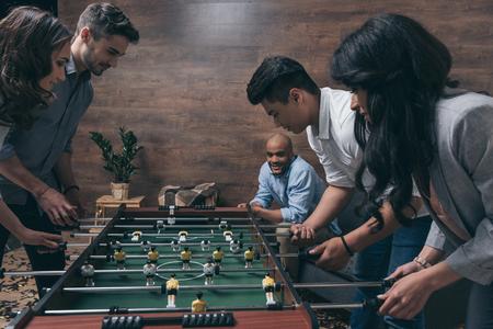 若いお友達一緒に室内テーブル ・ フットボールをプレー