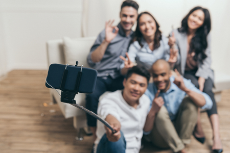 smiling multiethnic friends taking selfie with monopod and smartphone at home