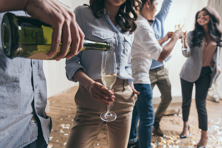 young man pouring champagne to stylish young woman at party