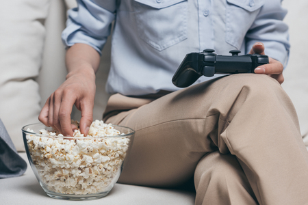 junky: woman eating popcorn while playing video games at home Stock Photo