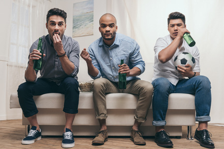 multiethnic friends drinking beer and watching football while sitting on sofa at home