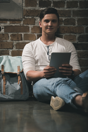 Man in casual clothes using digital tablet leaning to brick wall with backpack