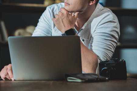 young man being lost in thought during work on laptop