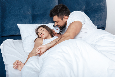 coverlet: young happy couple waking up with alarm clock in bed