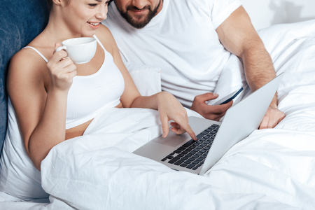 coverlet: young woman having coffee and using laptop with boyfriend in bed Stock Photo