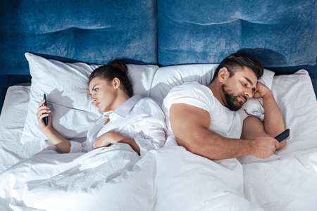 coverlet: young couple using smartphones in bed