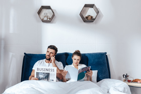 coverlet: young loving couple reading in bed Stock Photo