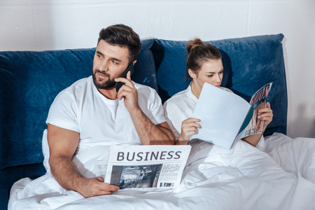 coverlet: Portrait of young loving couple reading in bed