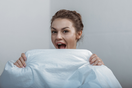 young smiling woman covering face with bedcover in bed Stock fotó