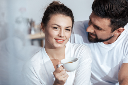 coverlet: young woman having coffee with boyfriend in bed