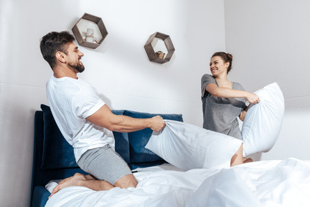 coverlet: young happy couple have battle of pillows in bed Stock Photo