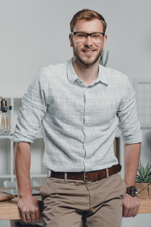 caucasian businessman looking at camera and leaning on table in modern office