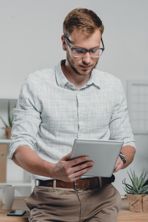 caucasian businessman using digital tablet and leaning on table in modern office Stock Photo
