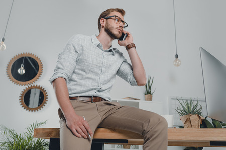 caucasian businessman using smartphone and leaning on table in modern office Stock Photo