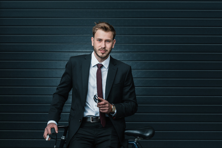 young businessman sitting on bicycle and holding sunglasses