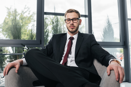 businessman in suit looking at camera while sitting on armchair at modern office