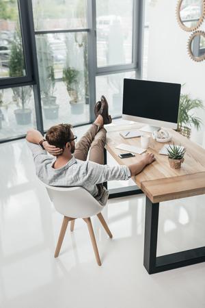 ビジネスマンのテーブルに座って、近代的なオフィスのコンピューターを使用して 写真素材