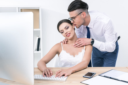 businessman whispering to his beautiful colleague during work at office