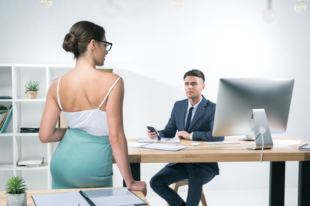 young businessman working at desk and looking at seductive businesswoman standing in office