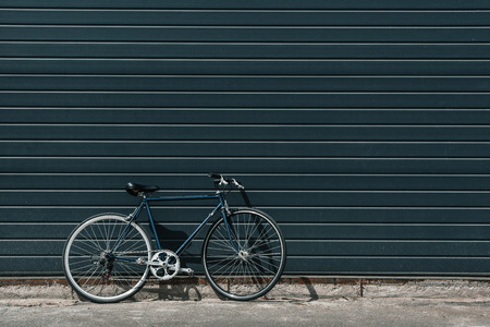 Black classic hipster bicycle standing near black wall outdoors Stock Photo