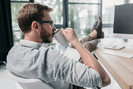 caucasian businessman drinking coffee while sitting at workspace