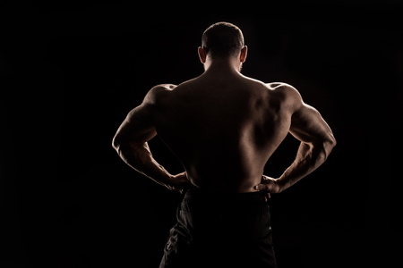 young shirtless athlete flexing back muscles Stock Photo