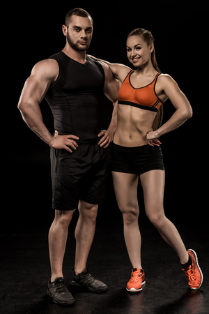 man and woman posing together and looking at camera isolated on black