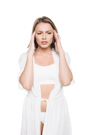 Portrait of young woman in white robe having huge headache Stock Photo