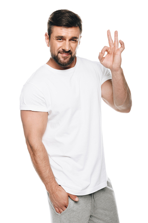 Portrait of handsome man in white t-shirt gesturing ok sign