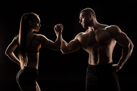 sporty couple holding hands isolated on black Stockfoto