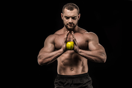 sportive man holding fresh apple isolated on black