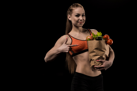 portrait of smiling woman pointing at bag with fresh vegetables Zdjęcie Seryjne - 83257975