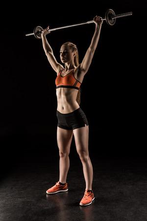 バーベルとスポーツウェア トレーニングで運動の若い女性